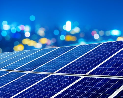 Photovoltaic panels in front of city night lights